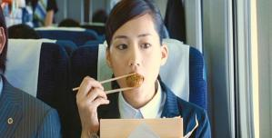 新幹線の中で弁当を食べている鳥居