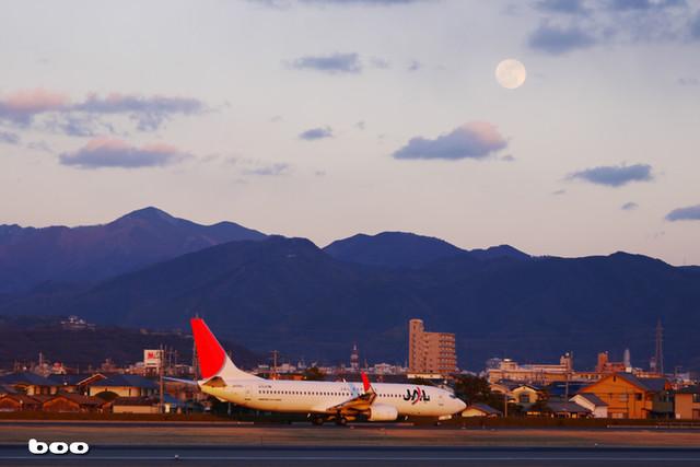 夕日を浴びる機体と月と