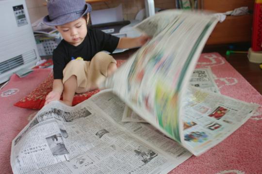 新聞を広げて読む次男