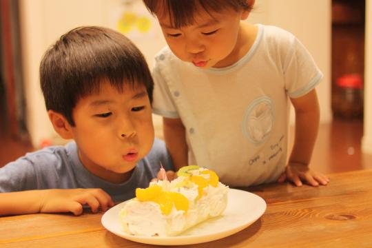 パパの誕生日ケーキを吹く二人