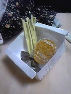 おつまみ。即席の紙箱にチー鱈とおせんべいとチョコレート。