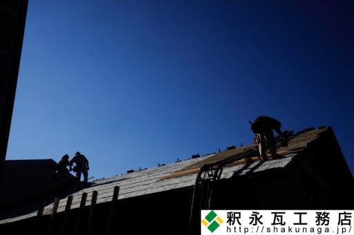釈永瓦工務店の従業員と秋の空、瓦屋根工事作業中